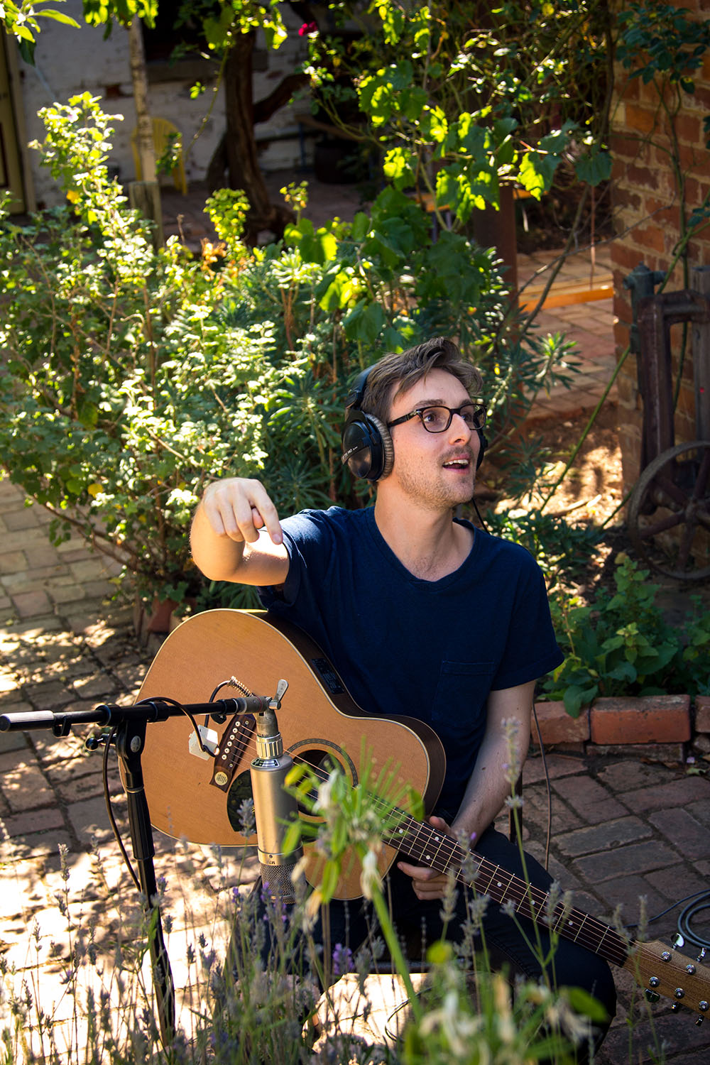 Sam Cromack recording his acoustic guitar out on the Sound Recordings patio to get a bit of separation and nature