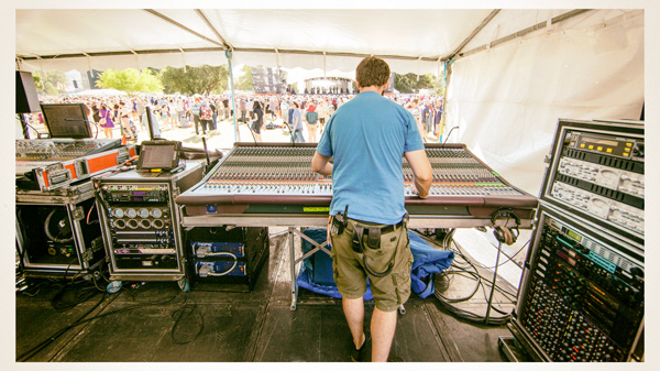 """At front of house on the main stage, Chris Braun works a Midas Heritage console. Nick Filsell (Production and Site Manager) discussed some production info: """"WOMADelaide is held together by approximately 65 AV techs. It takes about eight days to build the site from when we paint lines on the ground and tweak the layout to when we open the gates. Then about four and a half days to pack it all out. Novatech supply the audio visual equipment for WOMADelaide and everything on site is L-Acoustics Kudo."""""""